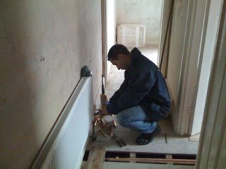Engineer fixing the radiators to the walls and linking up to the system